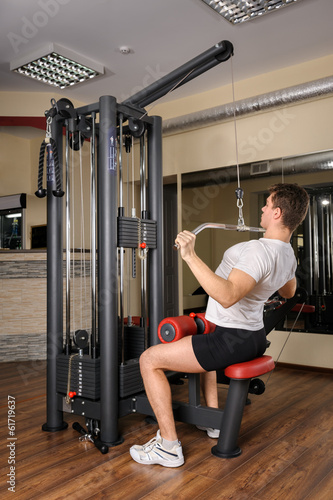 Young man doing lats pull-down workout in gym