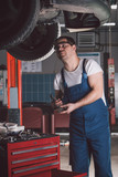 Car mechanic working in auto repair service poster