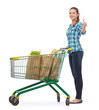 smiling young woman with shopping cart and food