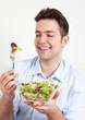 Lachender junger Mann bewundert seinen Salat