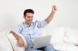 Jubelnder junger Mann mit Notebook auf dem Sofa