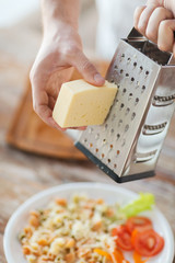 close up of male hands grating cheese over pasta