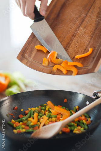 close up of male hand adding peppers to wok