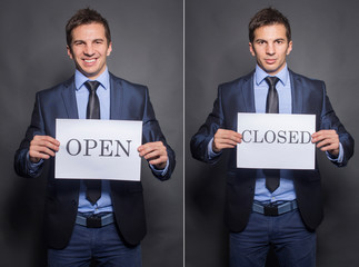 Businessman holding closed and open signs