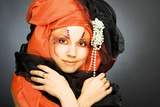 Young woman in black and orange turban
