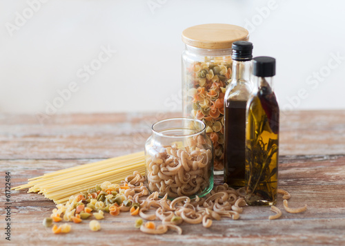 close up of two olive oil bottles and pasta in jar