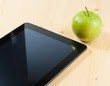 smart digital tablet pc and green apple on wood table