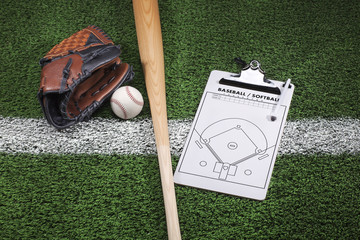 Baseball mitt, bat and clipboard on grass with stripe