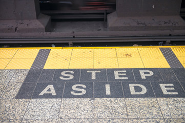 Step aside sign on a subway station
