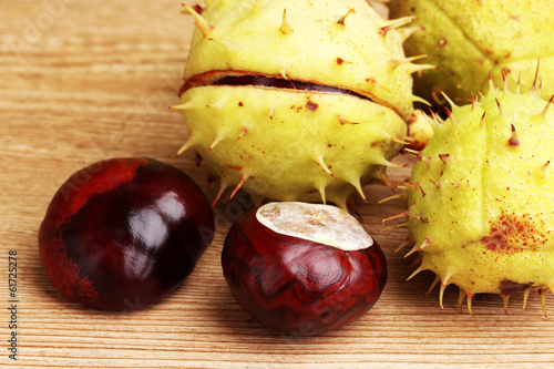 green and brown chestnuts on wooden background