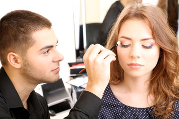 Young guy stylist doing makeup beautiful woman in beauty salon