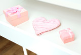 Gift boxes and heart in open desk drawer close up