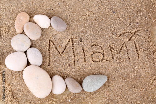 Inscription Miami in wet sand close-up background