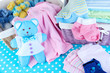 canvas print picture - Pile of baby clothes  in basket, on table on color background