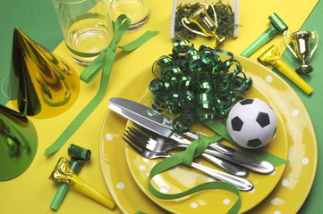 Soccer party table settings in yellow and green team colors.