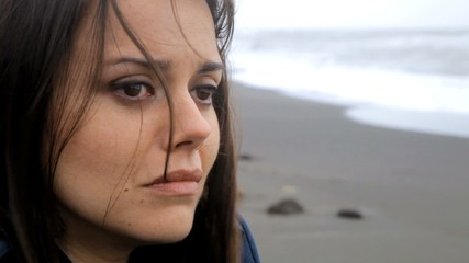 Closeup of sad woman crying on the beach