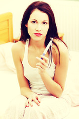 Sad woman holding a pregnancy test in the bedroom.