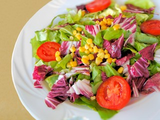 Colorful mixed salad with lettuce, tomatoes, cabbage and corn