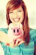 Teen woman showing her pink piggy bank