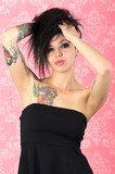 Suicide girl style tattooed woman in pink background
