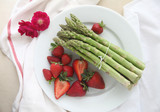 Asparagus with strawberries on plate