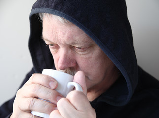 Older man in hoodie with coffee