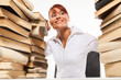Woman sitting by the desk with pile of books