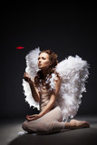 Charming young woman posing dressed as angel poster