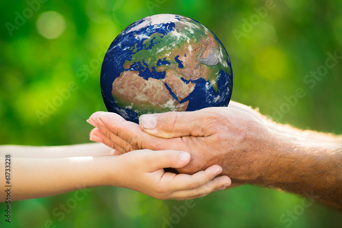 Child and man holding Earth in hands