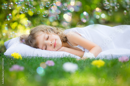 Kid sleeping in spring garden