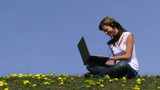 Young woman communicating via her laptop in a field