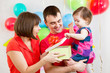 smiling kid girl with mother and father opening gift box