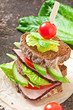 Sandwich with ham and fresh vegetables on a wooden background