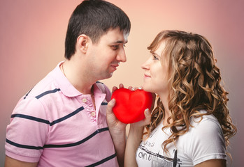 man and woman looking at each other and holding red heart
