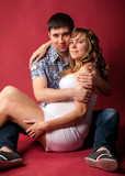 pregnant woman lying with husband on red background