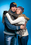 portrait of couple in warm clothes hugging and looking at camera