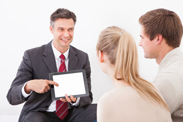 Salesman Showing Tablet Pc To Couple