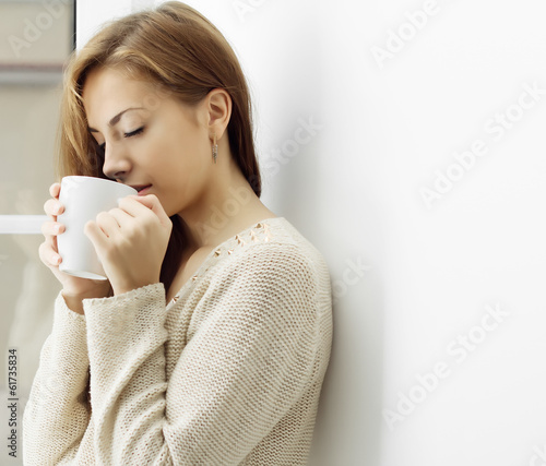 Girl with a cup in profile at the window