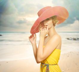 Beautiful girl in a hat enjoying the sun on the beach.