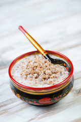 Buckwheat with milk served in a wooden khokhloma bowl