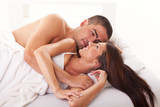 Young couple in love lying in bed and relaxing.