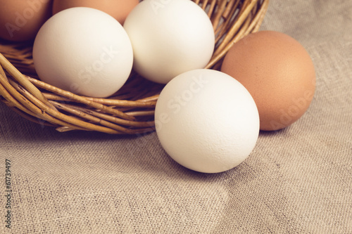 chicken eggs in basket on burlap