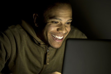 Man smiling on his laptop late at night