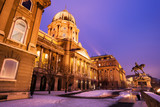 Snowy Buda Castle in Budapest under a purplish blue sky