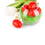 Easter eggs in a bowl with white tulips isolated on white