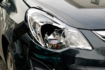 Broken headlamp on a black car