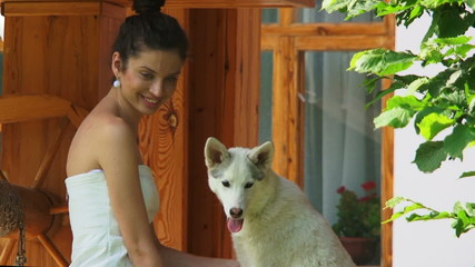 Young brunette petting a white dog