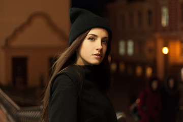 Beautiful girl in the evening in hat and coat