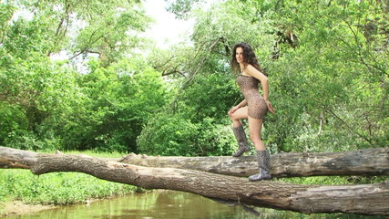 Woman posing for camera on a fallen tree