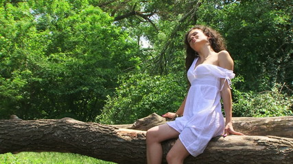 Young brunette sitting on a fallen tree